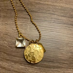 Gold Coach round locket never been used